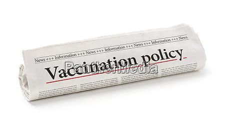 rollende zeitung mit der schlagzeile impfpolitik