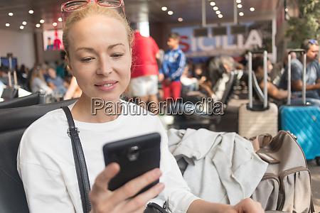 female traveler reading on her cell