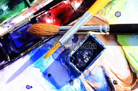 zwei gekreuzte aquarellpinsel ueber einem aquarell