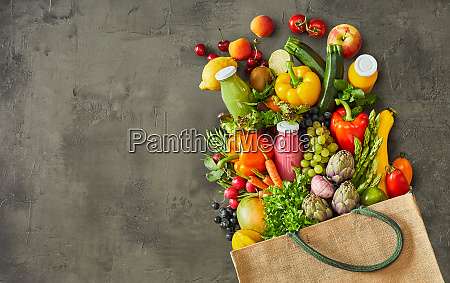 grocery bag with vegetables over grey