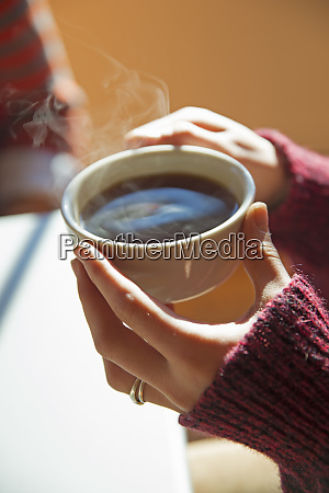 a woman holding a cup of