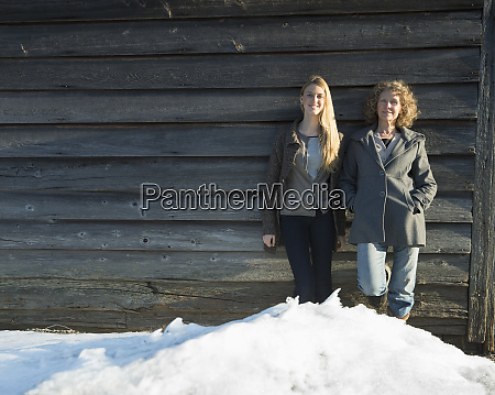 a mother and daughter standing leaning