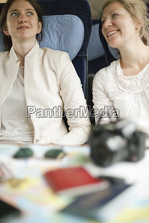 two women seated on a train