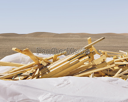 white tarp covering pile of wood