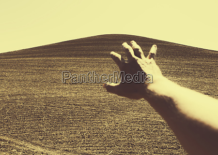hand extending towards ploughed farmland near