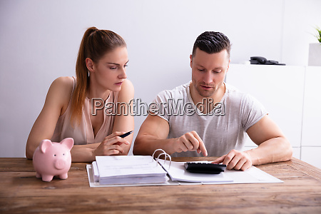 couple calculating bills using calculator near