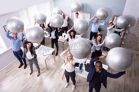 geschaeftsleute dehnen mit fitnessball im buero