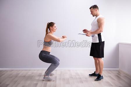 sportliche frau macht tiefe squat UEbung