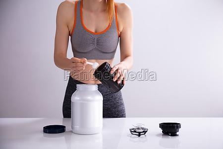 sportliche frau macht protein shake auf