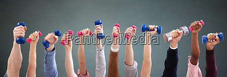 man and womans hand holding dumbbells