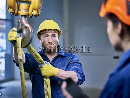 industriearbeiter befestigung hebegurt auf innenkran weibliche