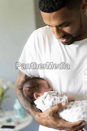 father holding his sleeping newborn baby