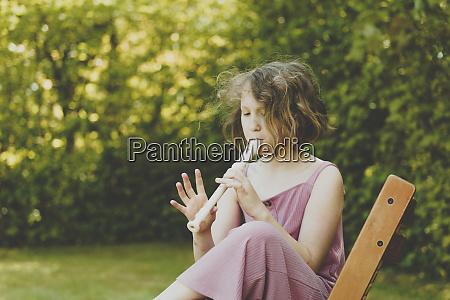 ein maedchen spielt floete im garten