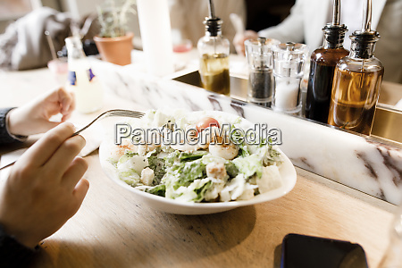 teenage boy eating a cersars salad