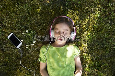 girl lying on meadow listening music