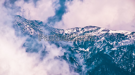 mountain top with scattered thick clouds
