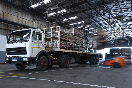 forklift loading crates on parked truck