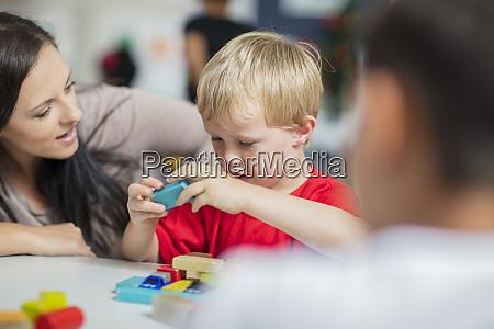 vorschullehrerin spielt mit kind im kindergarten