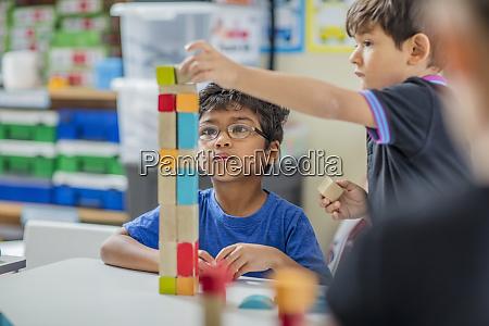 jungen stapeln bausteine im kindergarten