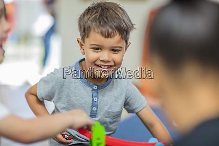 gluecklicher junge spielt mit anderen kindern