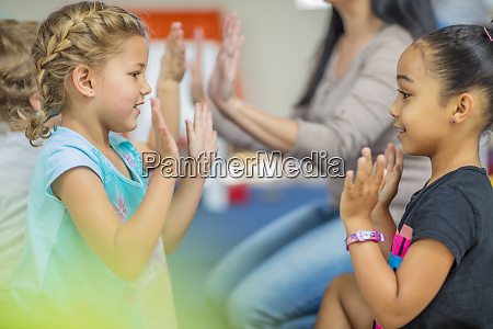glueckliche kinder und vorschullehrerin klatschen im