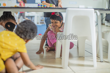 cheerful girls playing under the table