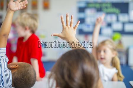raised hands of children in kindergarten