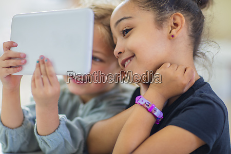two smiling girls sharing mini tablet