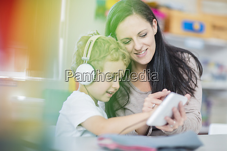 vorschullehrer zeigt mini tablet zu jungen