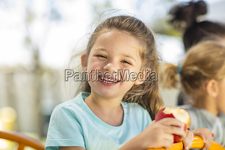 portraet von gluecklichen maedchen essen einen