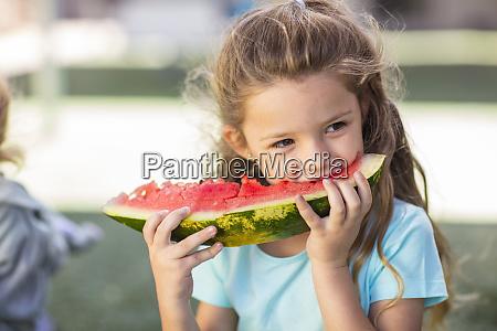 maedchen isst eine wassermelone im kindergarten