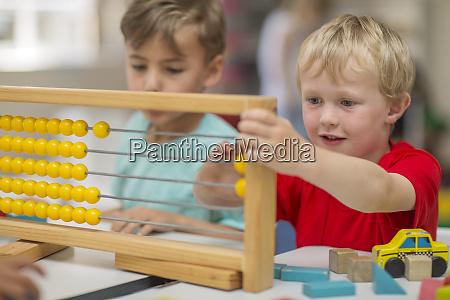 jungen im kindergarten mit abacus