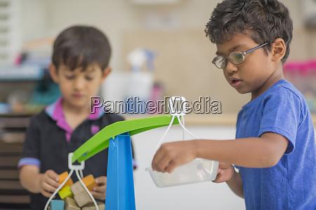 jungen spielen mit spielzeugwaage im kindergarten