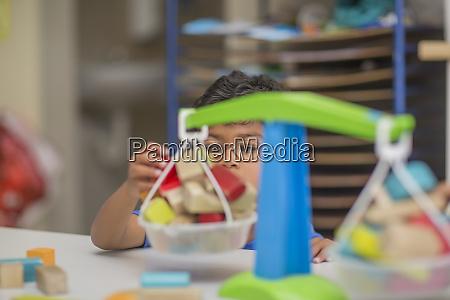 junge spielt mit spielzeugwaage im kindergarten