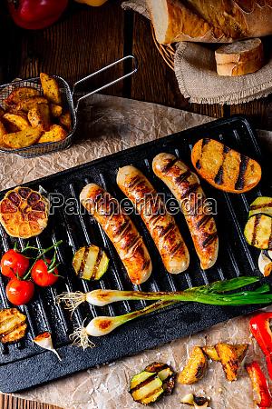 leckere grillwurst mit verschiedenen gegrillten gemuesesorten