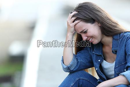 trauriges maedchen weint allein auf der