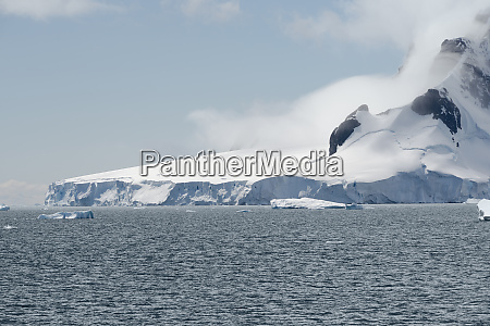 calving glacier and clouds covering the