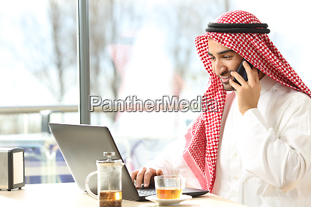 gluecklicher arabischer mann mit einem laptop