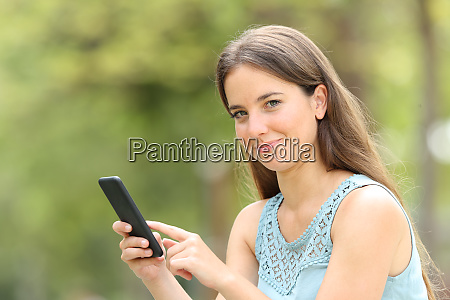 smiley woman holding smart phone looking
