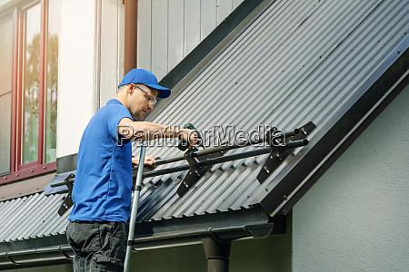 dachdecker installiert schneeschutz auf metalldach