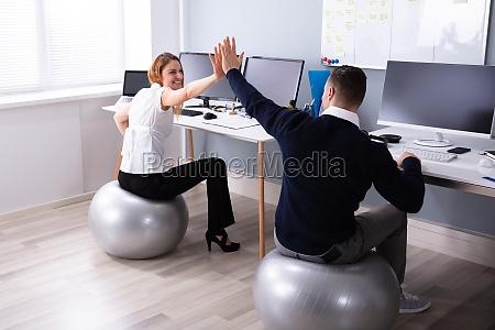geschaeftsleute sitzen auf fitness ball geben