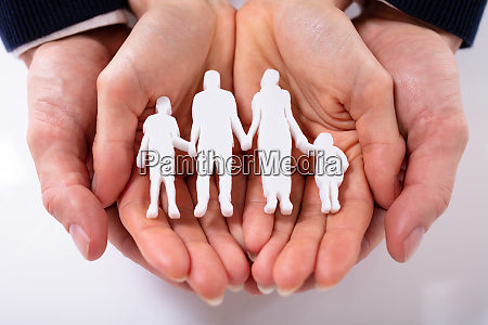 couples hand with family figure over