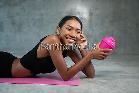 glueckliche gesunde laechelnde frau haelt protein