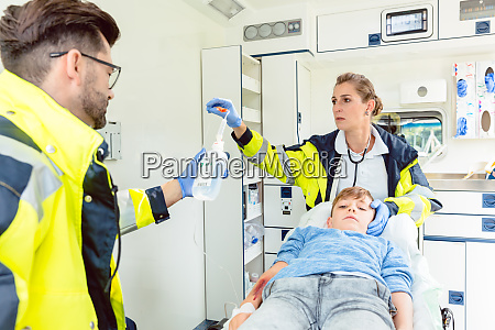 emergency doctor and paramedic giving infusion