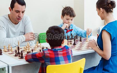 personen die ein schachturnier spielen