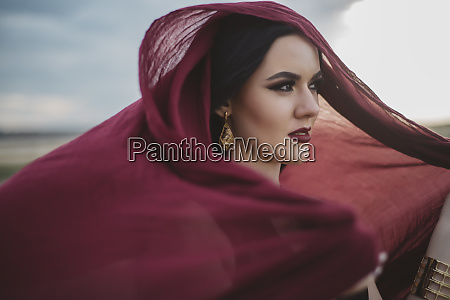 windswept woman wearing red headscarf and