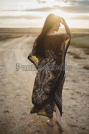 woman wearing patterned dress walking on