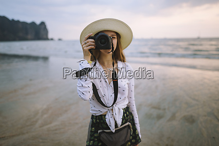 young woman photographing on beach in
