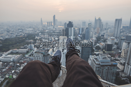 legs of young man and cityscape