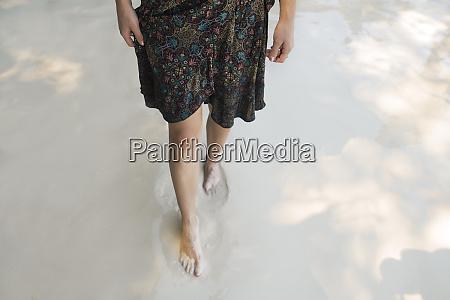 legs of woman walking on beach